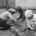 Lapset katua kraappaamassa Raahen Saaristokadulla 1923. Kuva: Samuli Paulaharju.